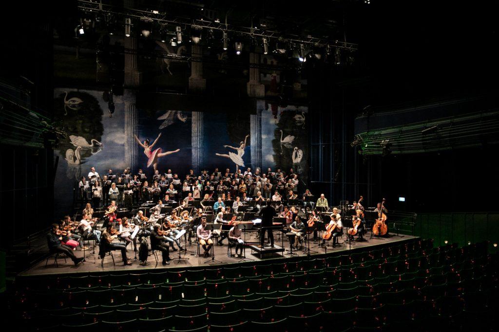 Widok z końca widowni. Z przodu publiczność widoczna tyłem. W oddali na scenie soliści, orkiestra i chór mieszany.