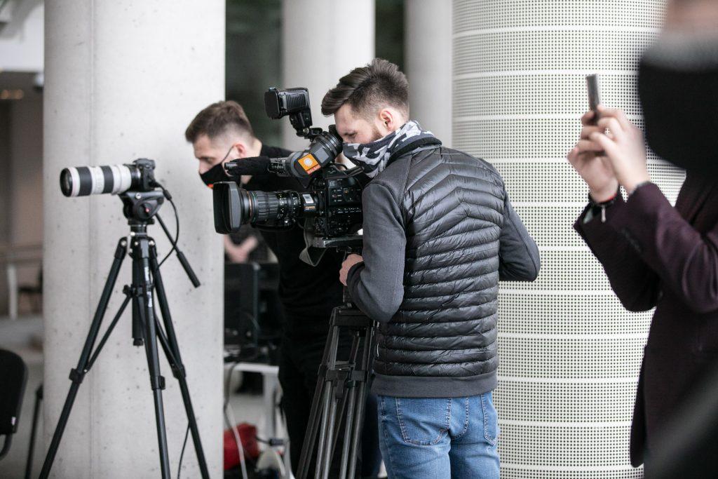 Dwóch mężczyzn w maseczkach ochronnych stoi przed kamerami na statywach.