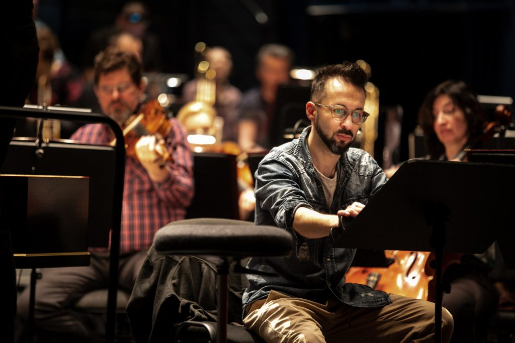 Zbliżenie na solistę podczas próby do koncertu. Za nim siedzi orkiestra.