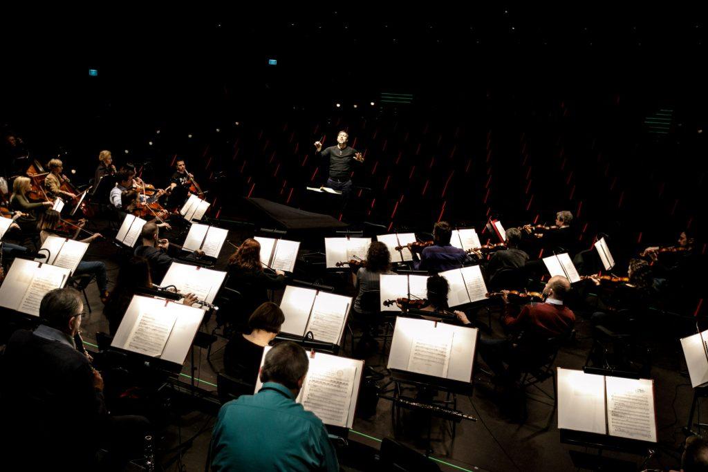 Na zdjęciu przy pulpitach z otwartymi nutami siedzi orkiestra. Na końcu stoi dyrygent. W oddali widoczna widownia.