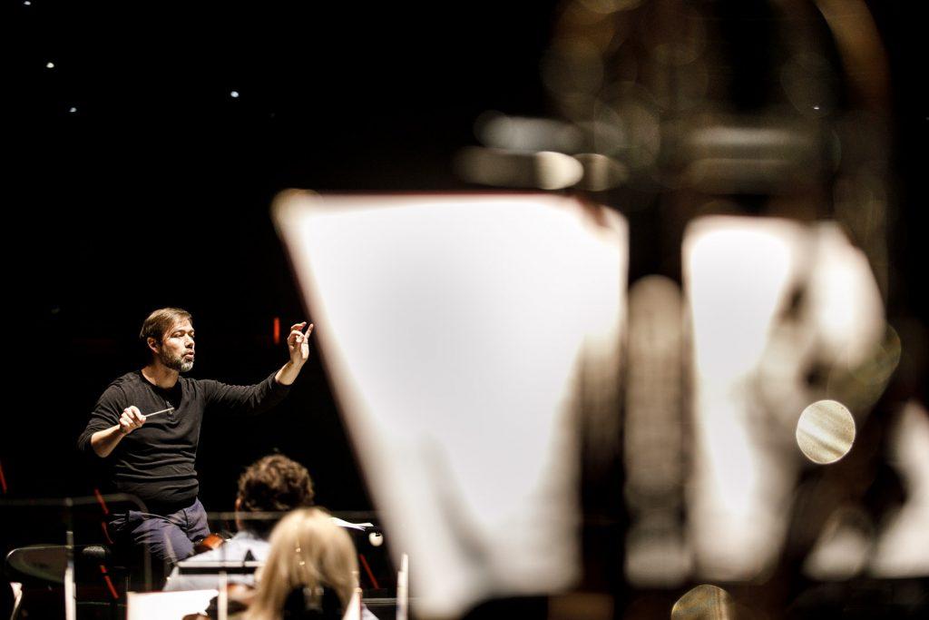 Zbliżenie na pulpity do nut. Za nimi widać dyrygenta podczas próby do koncertu.