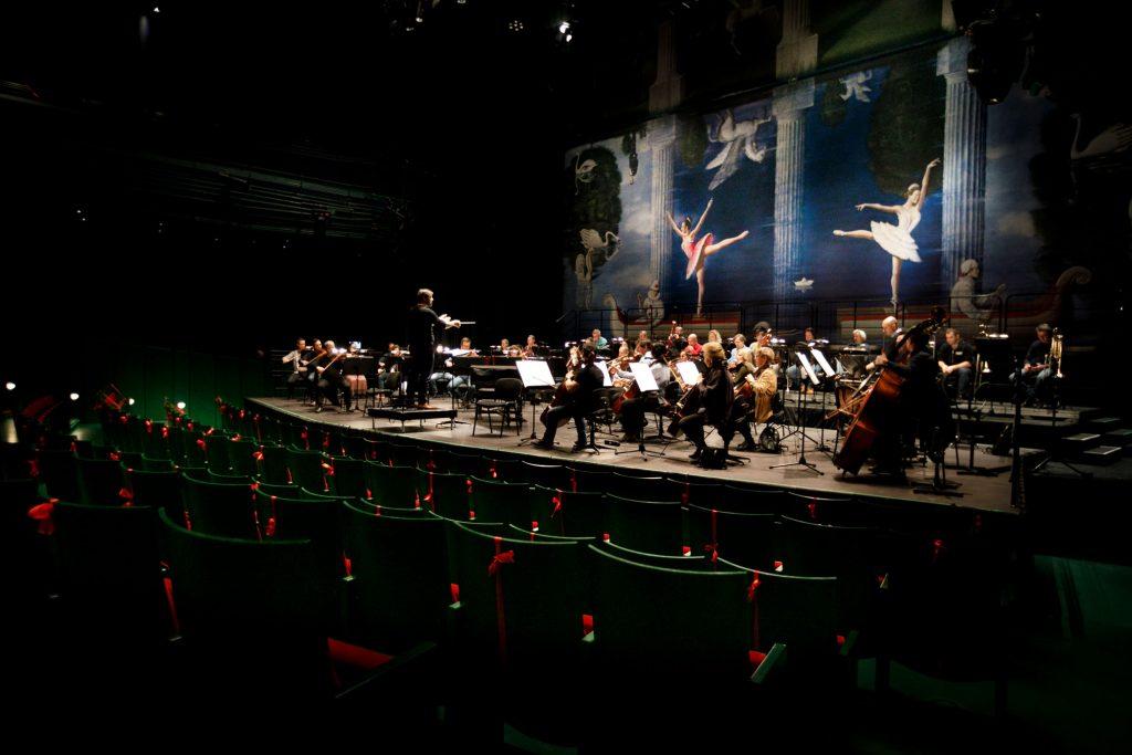 Zdjęcie zrobione z boku. Z przodu widać kilka rzędów widowni. Dalej na scenie orkiestra wraz z dyrygentem podczas próby do koncertu.