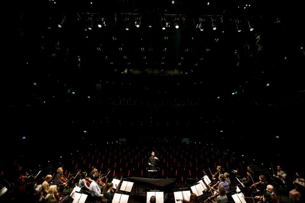 Widok ze sceny na widownię. Na dole na scenie widoczna część orkiestry. Na środku stoi dyrygent. Za nim widok na widownię.