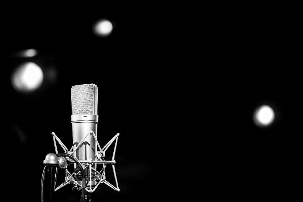 Na czarnym tle widoczny srebrny mikrofon.