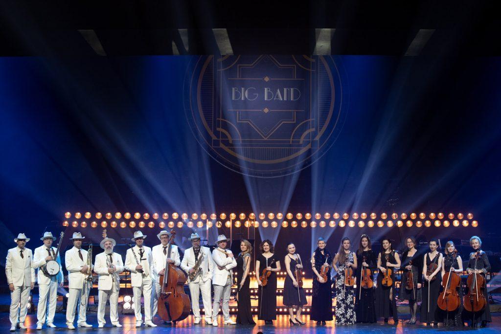 Widok na scenę. Na scenie od lewej ,z instrumentami, w białych garniturach stoi w rzędzie Big Band Opery i Filharmonii Podlaskiej. Dalej wzdłuż sceny stoi sekcja smyczkowa orkiestry . Za nimi podwójny rząd reflektorów. Nad nimi duży napis '' Big Band''.