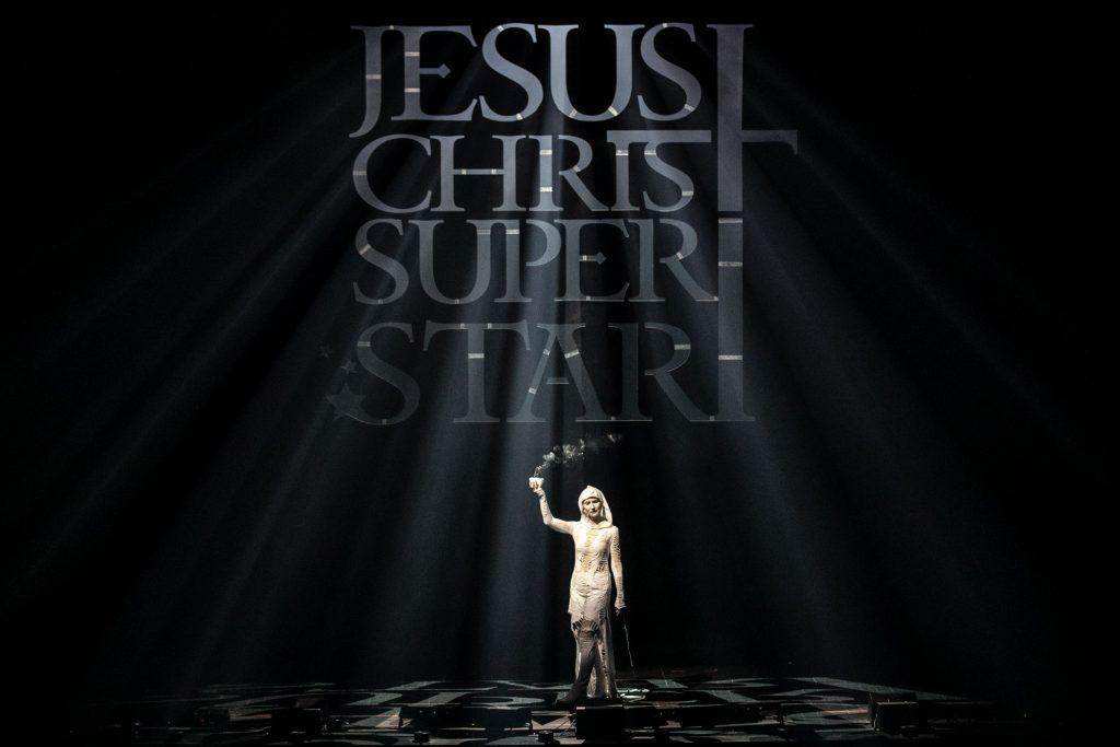 Na tle czarnej kotary z wyciętym napisem Jesus Christ Superstar stoi kobieta w białym kostiumie. W uniesionej ręce trzyma palące się kadzidło. Przez wycięty napis wpadają smugi światła.