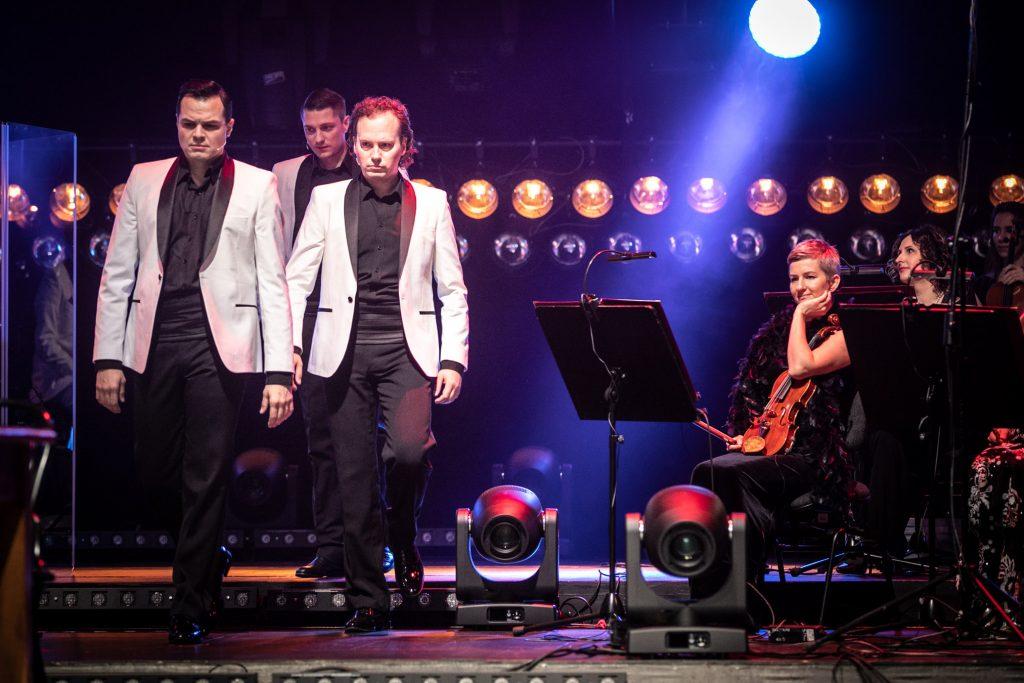 Na scenie, po lewej stronie trzech mężczyzn w białych marynarkach. Po prawej stronie, przy pulpitach do nut, siedzą muzycy z grupy skrzypiec. Dalej w dwóch rzędach wiszą okrągłe lampy.