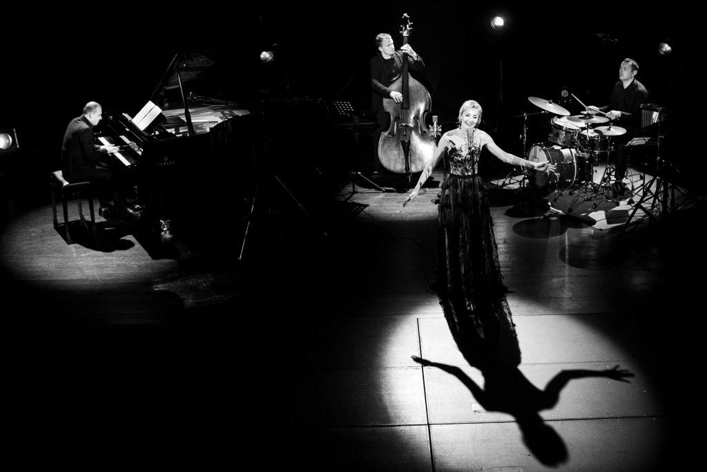 Zdjęcie czarno-białe. Na środku stoi kobieta w długiej sukni w smudze światła. Trzyma ręce rozłożone na boki. Za nią po lewej stronie siedzi mężczyzna przy fortepianie, obok mężczyzna grający na kontrabasie. Po prawej stronie siedzi mężczyzna przy perkusji.