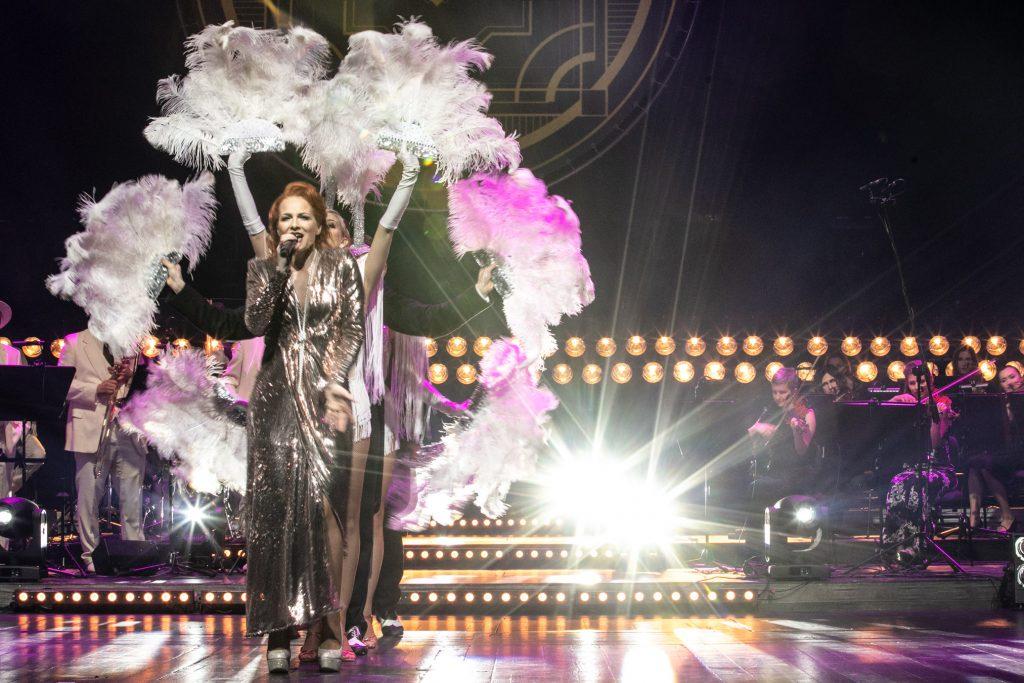 Scena oświetlona reflektorami. Na środku z mikrofonem stoi kobieta w długiej, srebrnej sukni. Za nia kilku tancerzy trzymający w rękach pióropusze. Za nimi po lewej widoczna część Big Bandu, po prawej część sekcji smyczkowej.