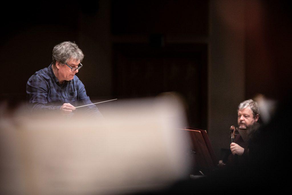 Na zdjęciu dwóch mężczyzn. Po lewej stronie dyrygent Oifp Prof. Mirosław Jacek Błaszczyk. Po prawej stronie jeden z muzyków orkiestry z sekcji smyczkowej.
