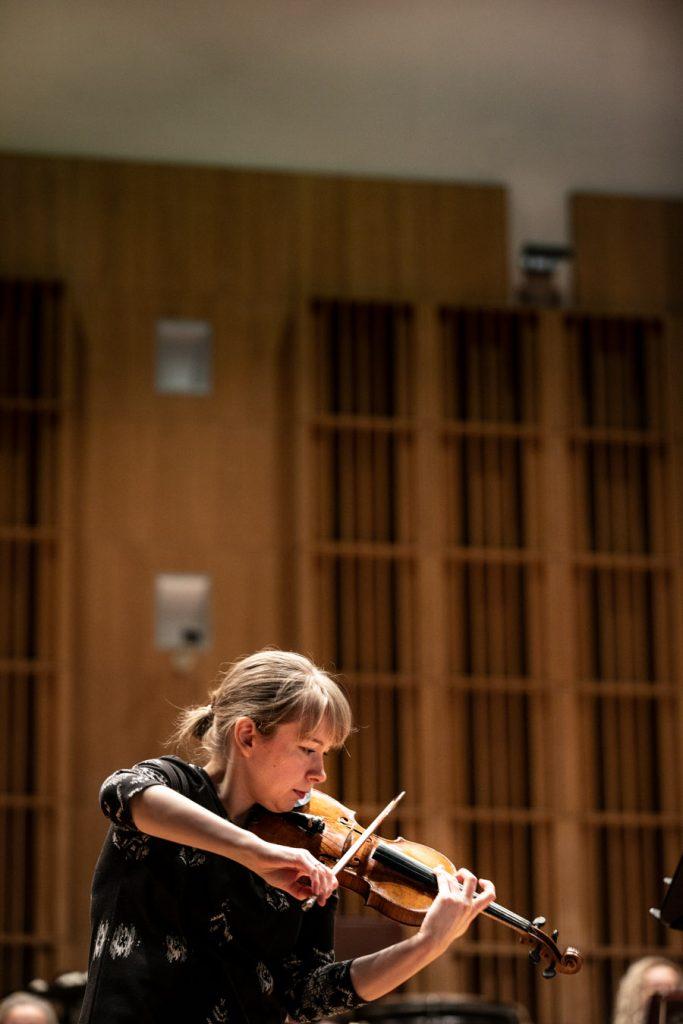 Na scenie solistka grająca na skrzypcach podczas próby do koncertu.