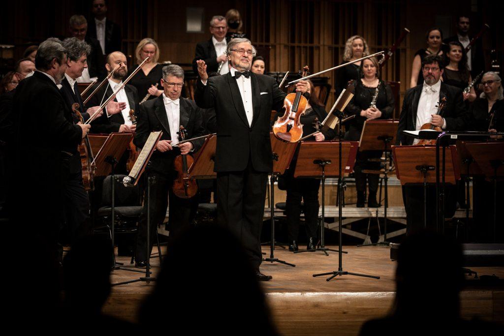 Solista z uniesionymi na boki rękoma stoi na scenie. Za nim stoi orkiestra.