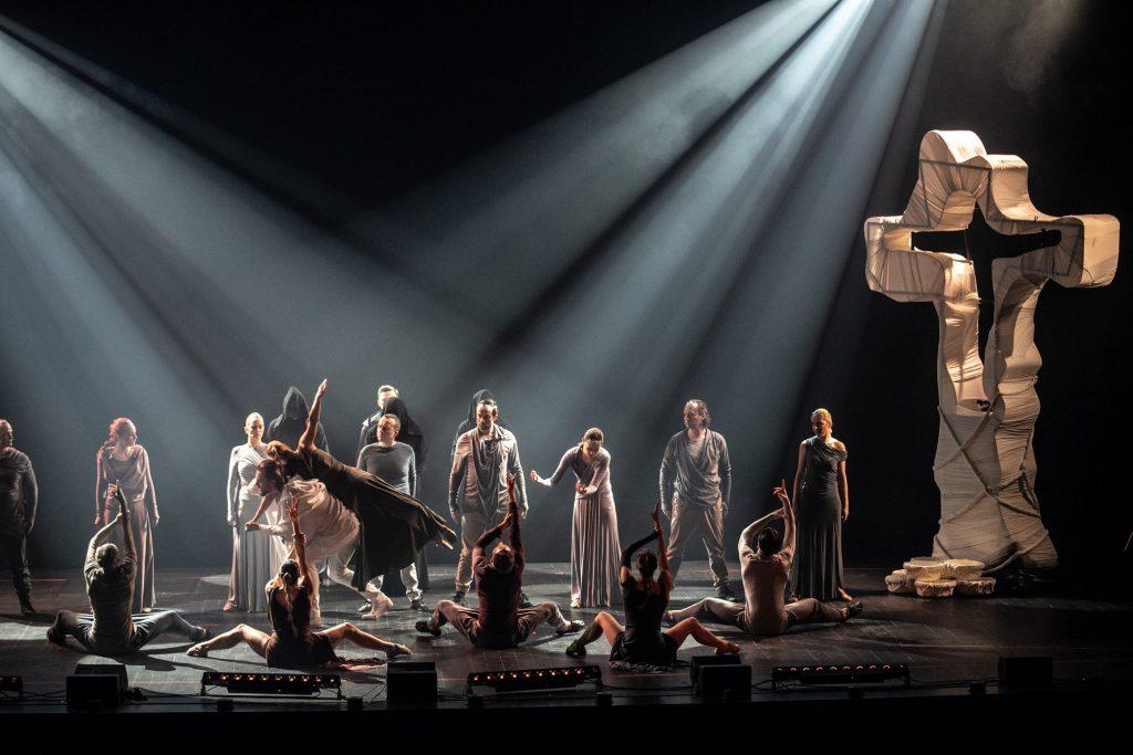 Scena oświetlona dwoma reflektorami świecącymi z góry rozproszonym światłem. Na środku mężczyzna niesie kobietę na ramionach. Za nimi stoi kilka osób zwróconych w ich kierunku. Przed nimi kilka osób siedzi na scenie w pozycjach tanecznych. Po prawej stronie stoi metalowy krzyż owinięty białym materiałem.