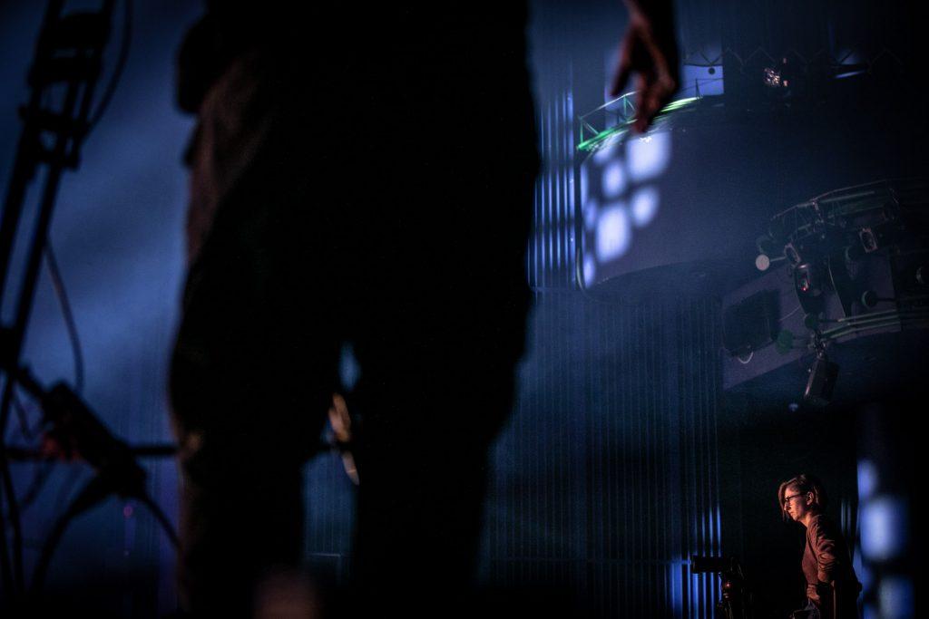 Scena w półmroku. Widok na bok sceny. Po prawej stronie stoi kobieta. Z przodu zbliżenie na męską sylwetkę.