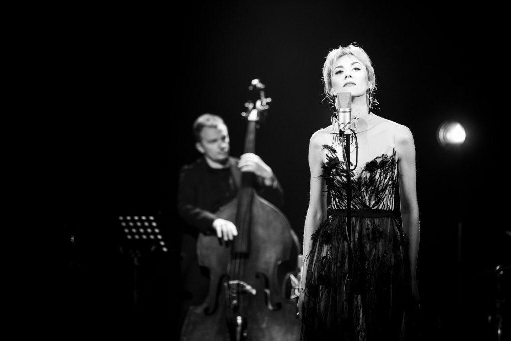 Zdjęcie czarno-białe. Przy mikrofonie stoi kobieta w długiej sukni. Patrzy przed siebie. Za nia widoczny mężczyzna grający na kontrabasie.