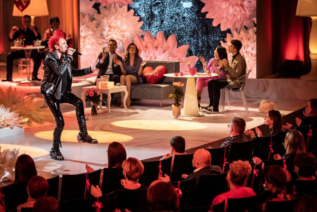Walentynki z Polsatem. Zbliżenie na scenę. Na niej z mikrofonem Michał Wiśniewski. Dalej przy stolikach i na sofie siedzą artyści biorący udział w widowisku. Z przodu widoczna część publiczności.