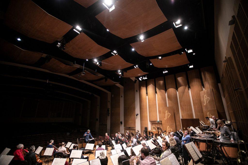 Próba do koncertu. Zdjęcie zrobione z rogu sceny. Przed pulpitami siedzi orkiestra Opery i Filharmonii Podlaskiej z dyrygentem.