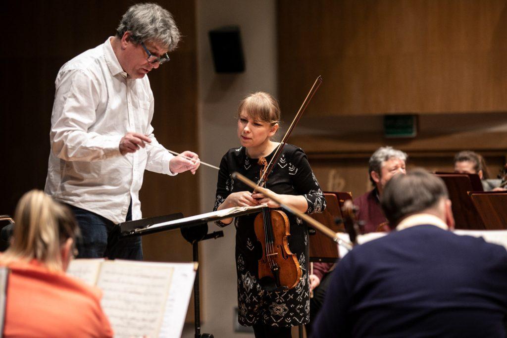 Próba do koncertu. Na podeście stoi dyrygent. Obok stoi solistka trzymająca skrzypce. Wokół siedzi część muzyków orkiestry.