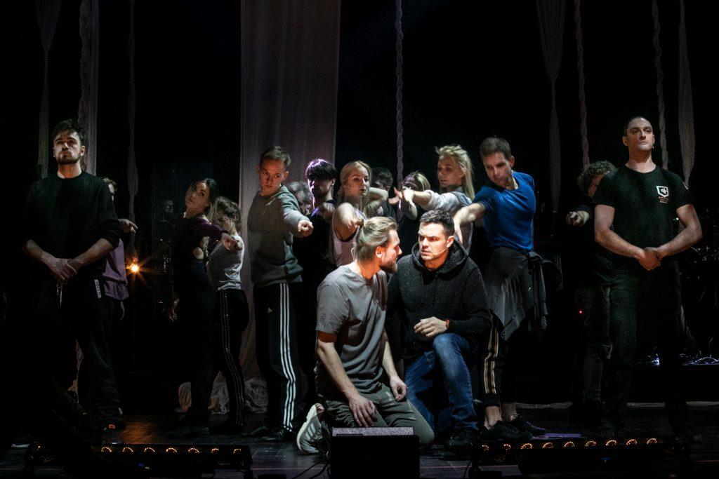 Próba do musicalu Jesus Christ Superstar. Dwóch mężczyzn klęczy obok patrząc w swoim kierunku. Za nimi stoi grupa tancerzy z wyciągniętymi rękami.