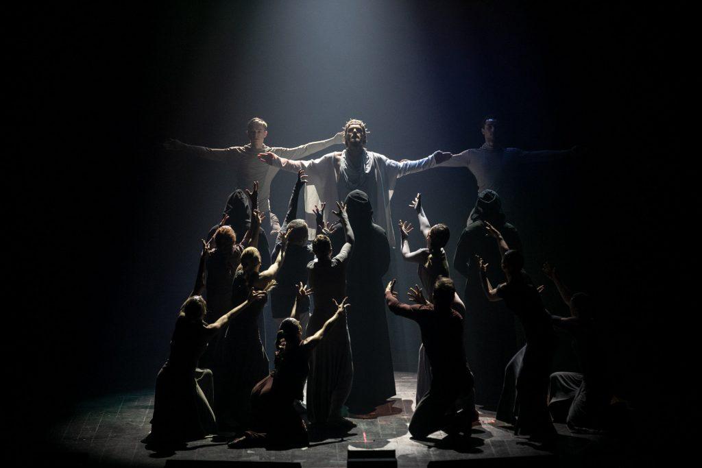 Na scenie półmrok. W jasnej łunie światła stoi mężczyzna w białym kostiumie z koroną cierniową na głowie. Ręce ma rozłożone na boki. Za nim po obydwu stronach stoi dwóch mężczyzn ubranych na biało z tak samo rozłożonymi rękami. Przed nimi kilkanaście osób stoi przodem z rękami wyciągniętymi w ich stronę.
