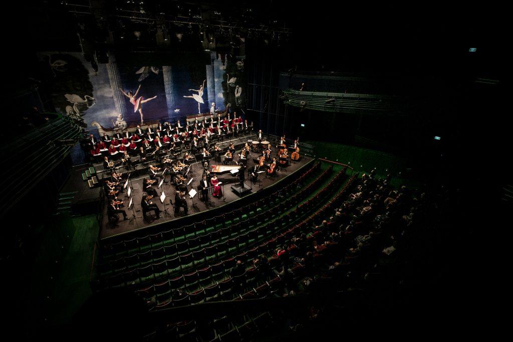 Widok z balkonu. Po prawej stronie publiczność na widowni. Na scenie trwa koncert ''Stworzenie Świata''.