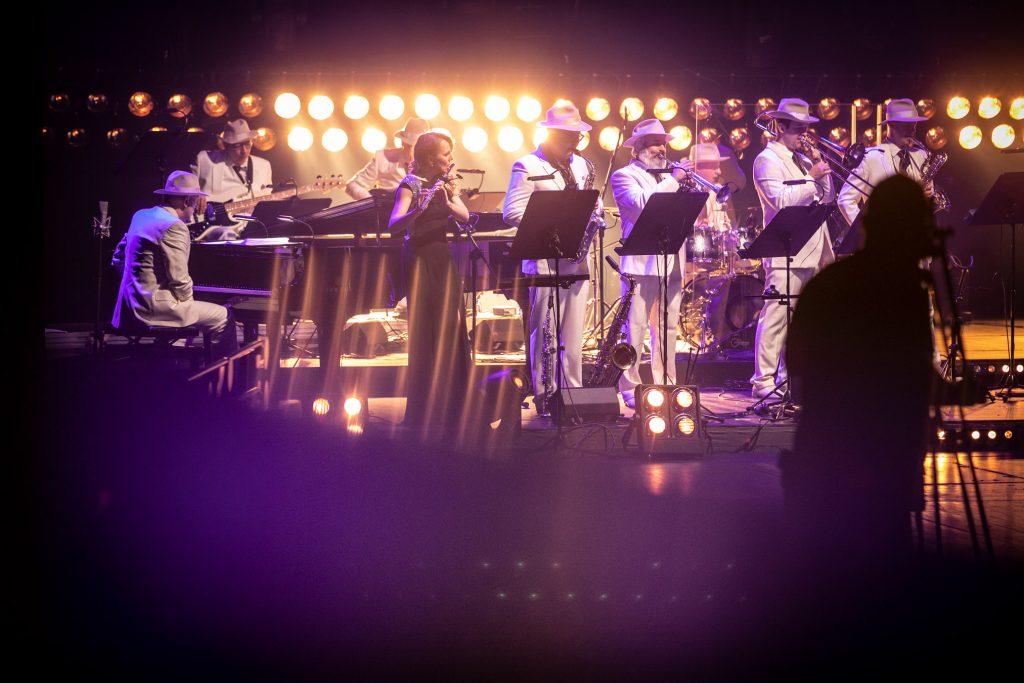Scena oświetlona fioletowym światłem. Na niej Big Band Opery i Filharmonii Podlaskiej. Z przodu czterech mężczyzn gra na instrumentach dętych, obok stoi kobieta grająca na flecie. Po lewej stronie siedzi mężczyzna przy fortepianie, dalej dwóch mężczyzn grających na gitarach. Na końcu widoczna perkusja przy której siedzi mężczyzna. W oddali w dwóch rzędach świecące okrągłe lampy.