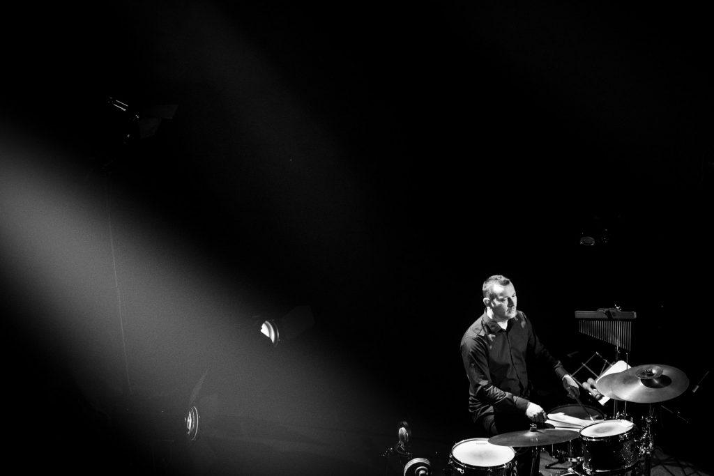 Zdjęcie czarno-białe. Po prawej stronie w rogu kadru siedzi mężczyzna przy perkusji. Dookoła czarne tło. Po lewej stronie widać dwa reflektory w jasnej smudze światła.