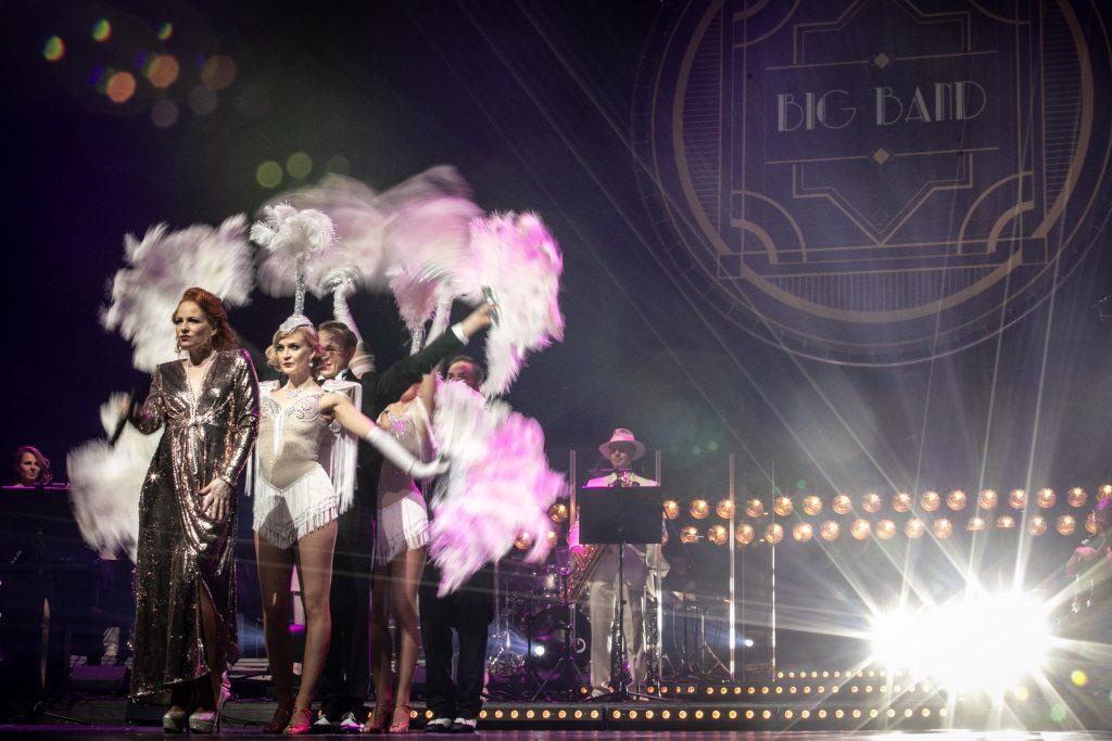 Scena oświetlona reflektorami. Zdjęcie zrobione z boku. Z przodu stoi kobieta w długiej, srebrnej sukni. Za nią kilku tancerzy trzymający w rękach pióropusze. Za nimi po lewej widoczna część Big Bandu. Na górze iluminacja świetlna i napis ''BIG BAND''.