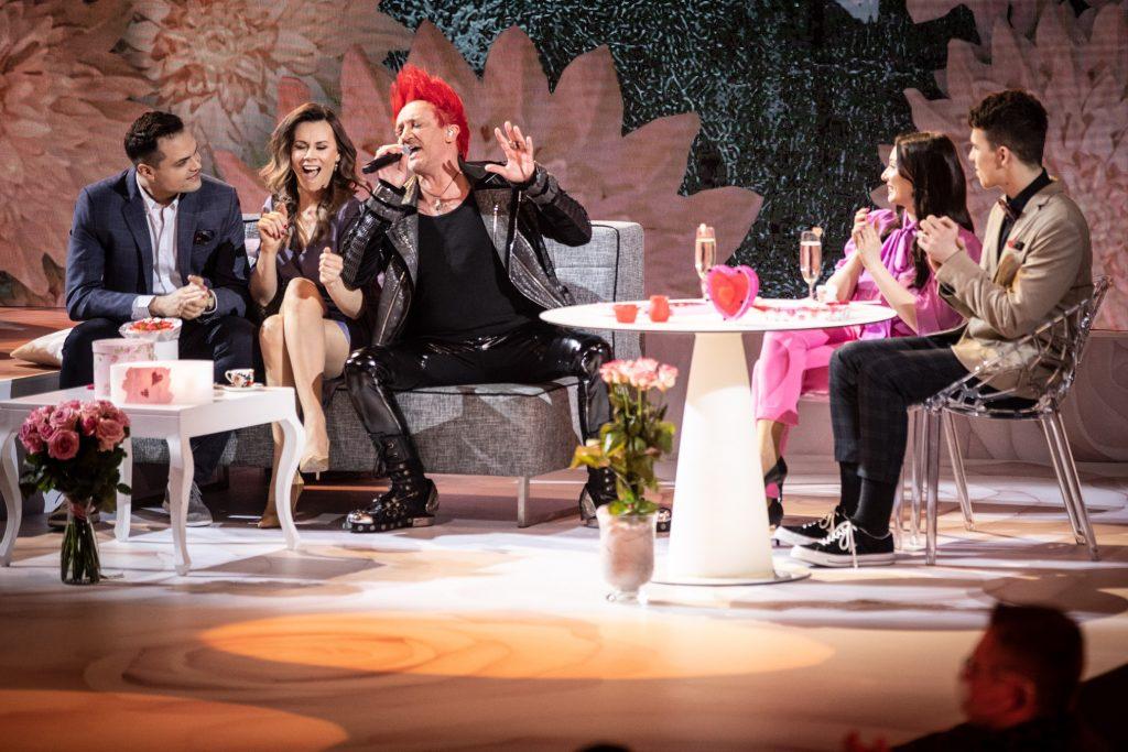 Na szarej sofie siedzi mężczyzna z czerwonymi włosami. Śpiewa do mikrofonu. Obok siedzi para. Po prawej stronie przy stoliku z szampanem siedzi kobieta i mężczyzna.