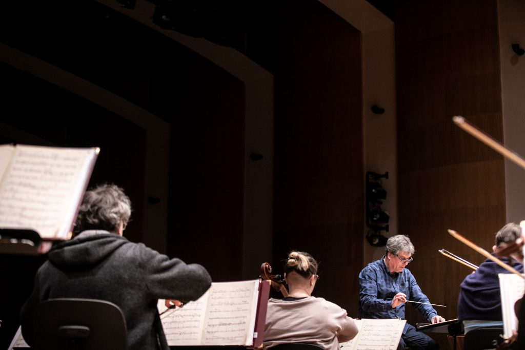 Próba do koncertu. Na scenie siedzi tyłem część sekcji smyczkowej. Dalej przed pulpitem siedzi dyrygent.