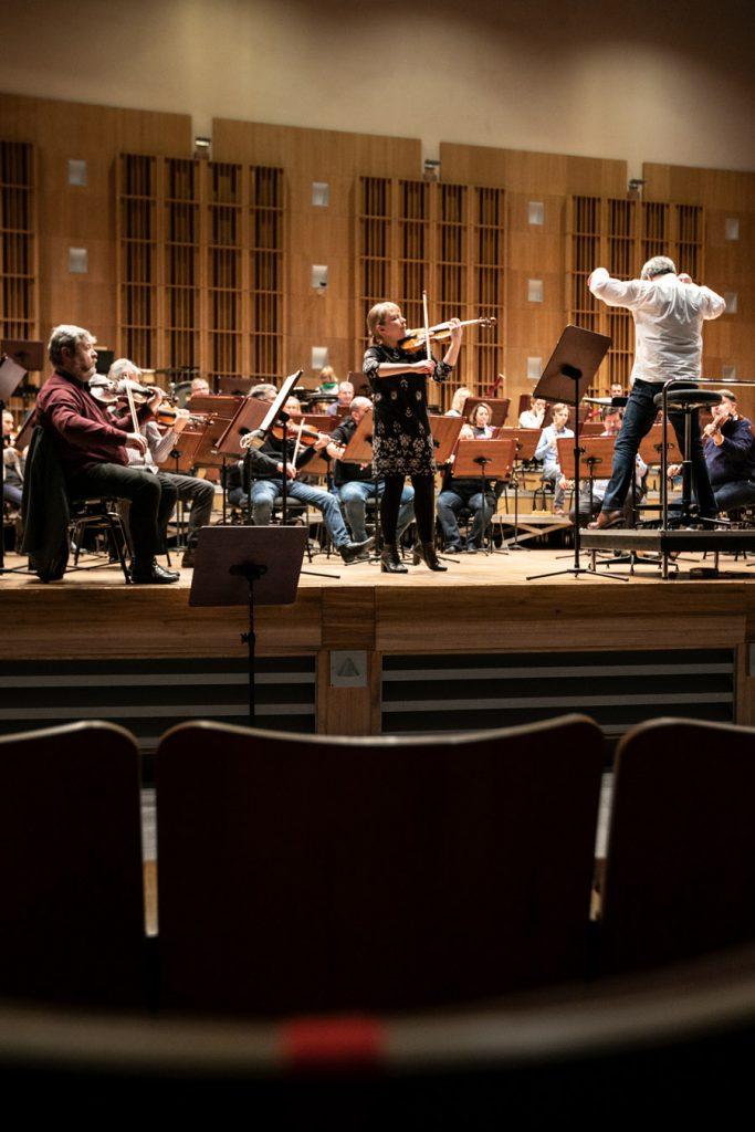 Zdjęcie zrobione z widowni. Na scenie orkiestra podczas próby do koncertu. Na środku stoi solistka grająca na skrzypcach. Obok niej na podeście stoi dyrygent.