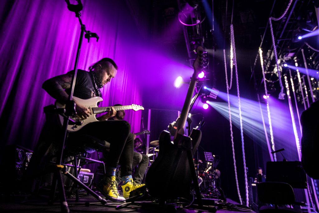 Na tle fioletowego światła mężczyzna gra na gitarze elektrycznej.