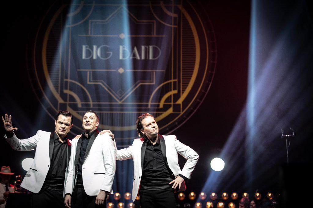 Trzech mężczyzn w białych marynarkach stoi obok siebie. Za nimi widoczny duży napis ''Big Band''.