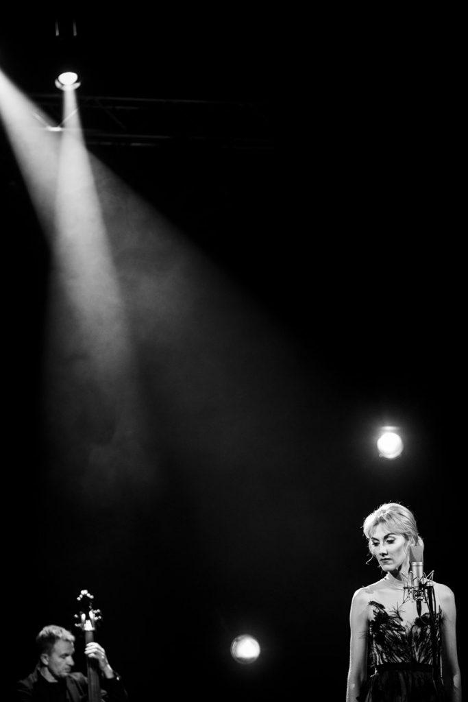 Zdjęcie czarno-białe. W rogu kadru po prawej stronie stoi kobieta w sukni. Po lewej stronie w rogu widać mężczyznę grającego na instrumencie smyczkowym. Z góry widoczne przecinające dwie smugi światła.