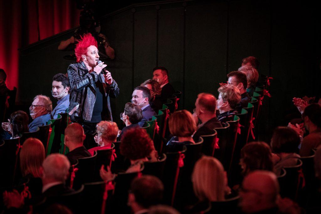Zbliżenie na publiczność siedzącą na widowni. Pomiędzy nimi z mikrofonem - Michał Wiśniewski.