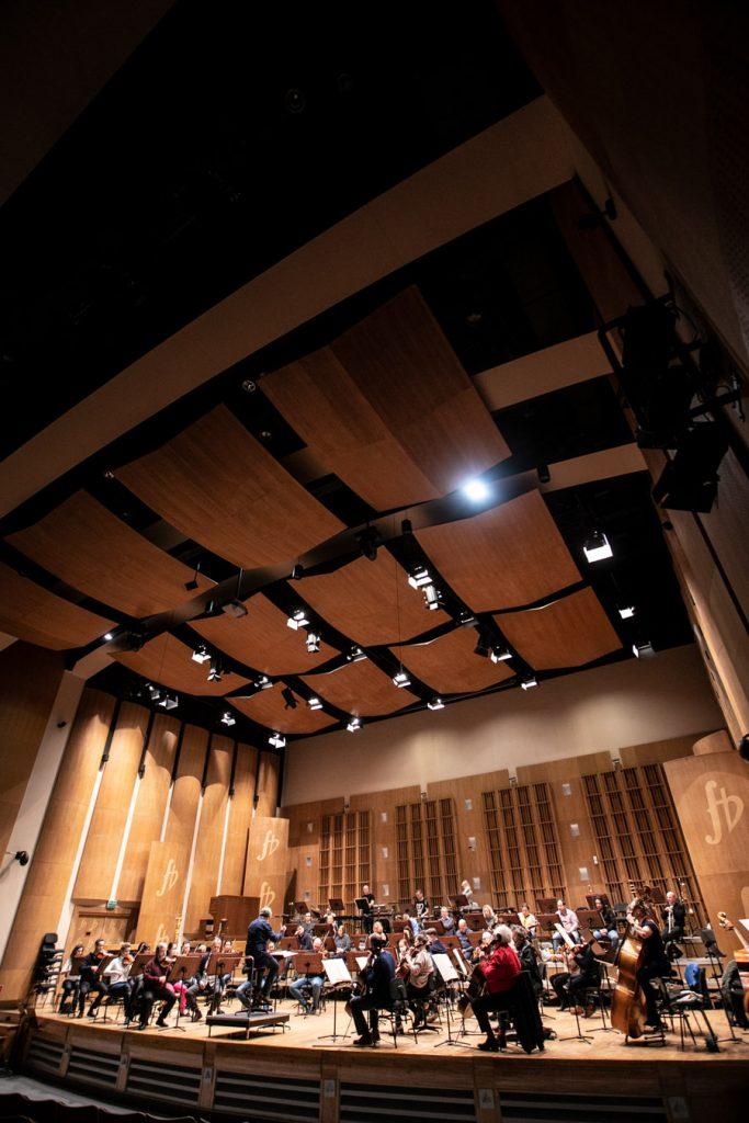 Zdjęcie zrobione z końca widowni. Na scenie orkiestra Opery i Filharmonii Podlaskiej podczas próby do koncertu.