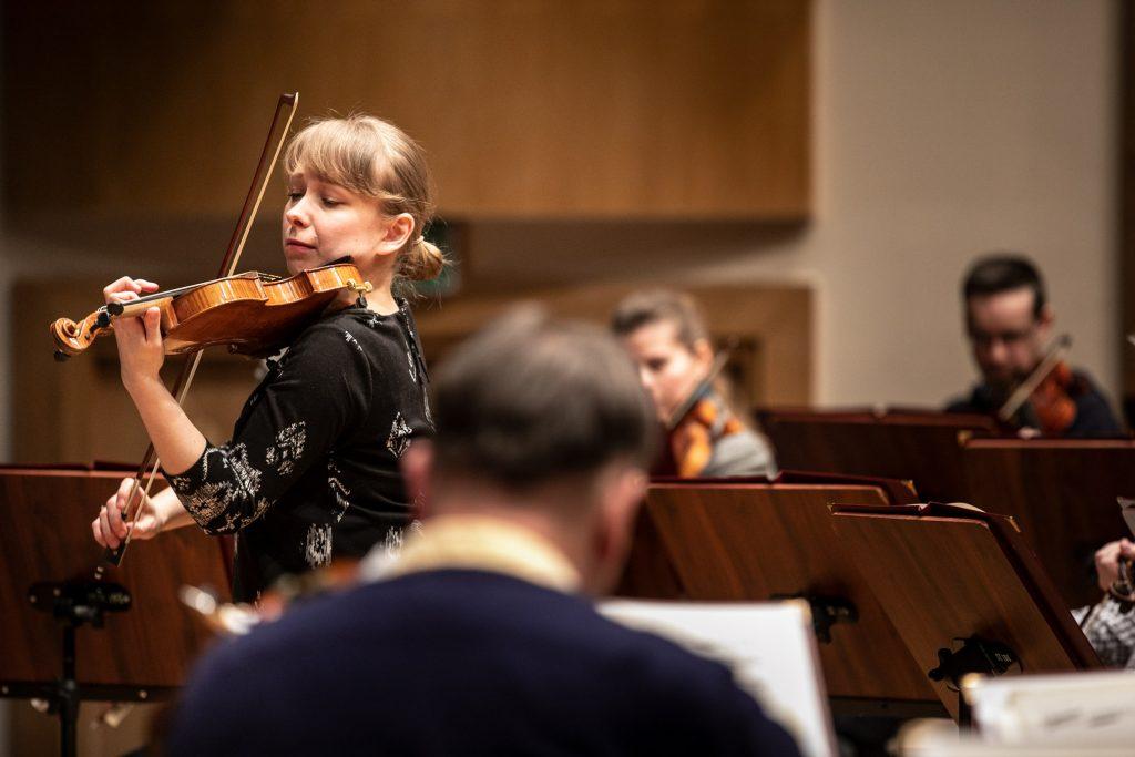 Solistka grająca na skrzypcach podczas próby. Za nia widoczna część sekcji smyczkowej.
