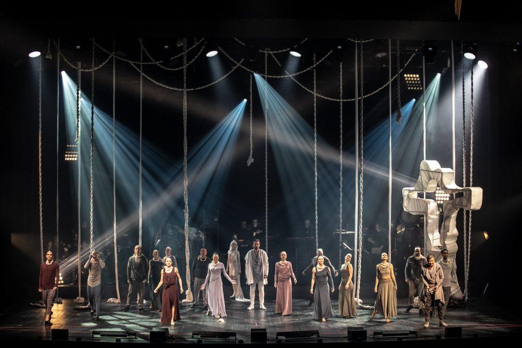 Na scenie stoi kilkanaście osób w różnych odstępach. Na środku stoi mężczyzna ubrany na biało. Po prawej stronie stoi metalowy krzyż owinięty białym materiałem. Z górnych reflektorów widoczne smugi białego światła.