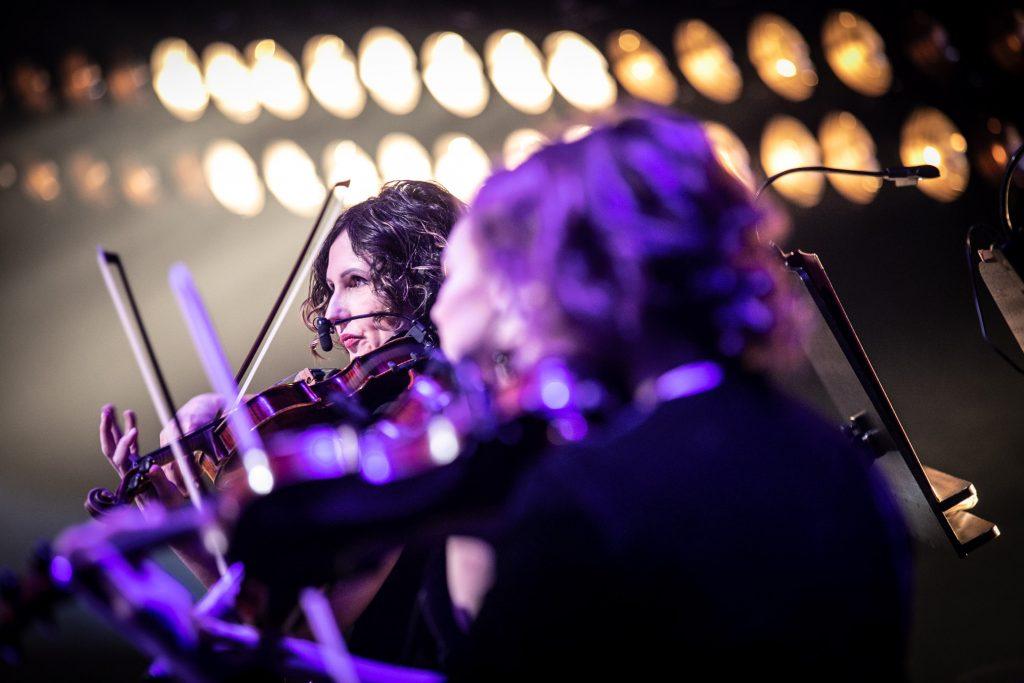 Zbliżenie na dwie kobiety grające na skrzypcach. Za nimi dwa rzędy świecących reflektorów.