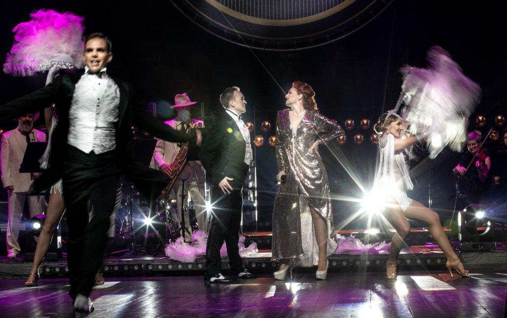 Scena oświetlona biało-fioletowym światłem. Na środku stoi kobieta w srebrnej sukni, zwrócona przodem do mężczyzny w czarnym garniturze. Po prawej stronie kobieta z pióropuszem w pozycji tanecznej. Po lewej stronie mężczyzna i kobieta z pióropuszem. W oddali widoczny Big Band Opery i Filharmonii Podlaskiej.