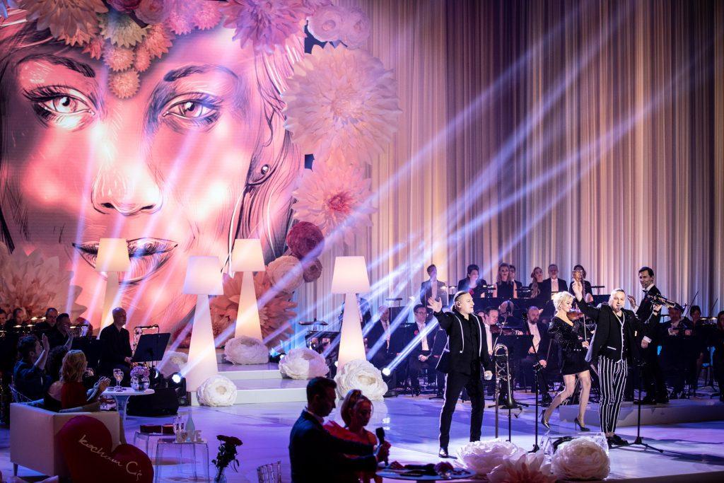 Scena Opery i Filharmonii Podlaskiej. Trwa koncert ''Walentynki z Polsatem''. Na niej zespół Golec Orkiestra i Orkiestra Tomasza Szymusia. Pomiędzy nimi duże, białe lampki. Z tyłu wyświetlona kobieca twarz.