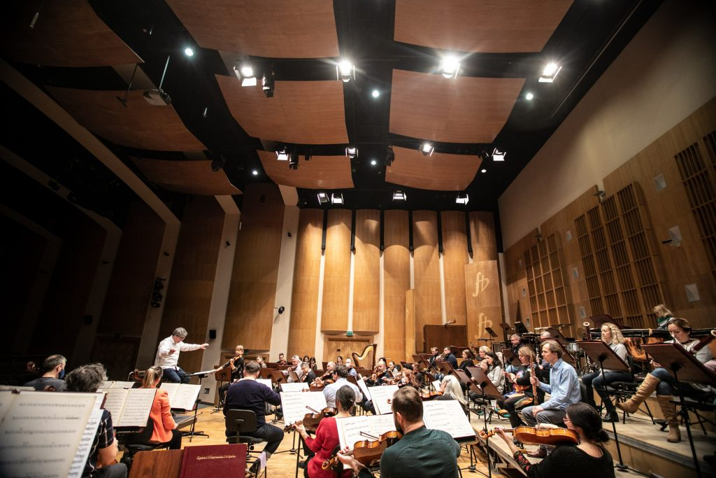 Próba do koncertu. Na scenie przed pulpitami siedzi orkiestra. Przed nimi dyrygent.