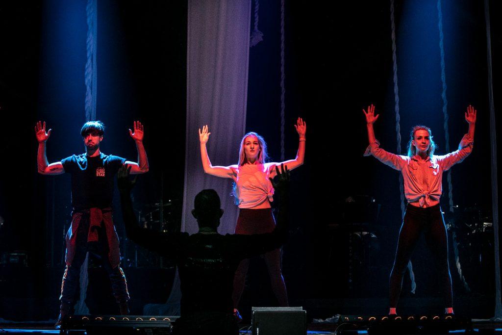 Trzy osoby stoją na scenie z szeroko rozstawionymi nogami. Ręce trzymają uniesione do góry dłońmi do przodu. Przed nimi pod sceną stoi tyłem mężczyzna z tak samo ułożonymi rękoma. Z tyłu widoczne podwieszone liny.