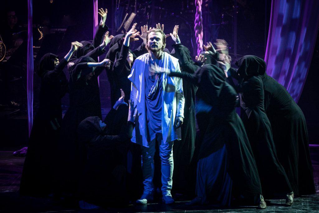 Scena oświetlona niebieskim światłem. Na środku stoi mężczyzna ubrany na biało. Wokół niego kilkanaście osób w czarnych płaszczach z wyciągniętymi rękami w jego stronę.