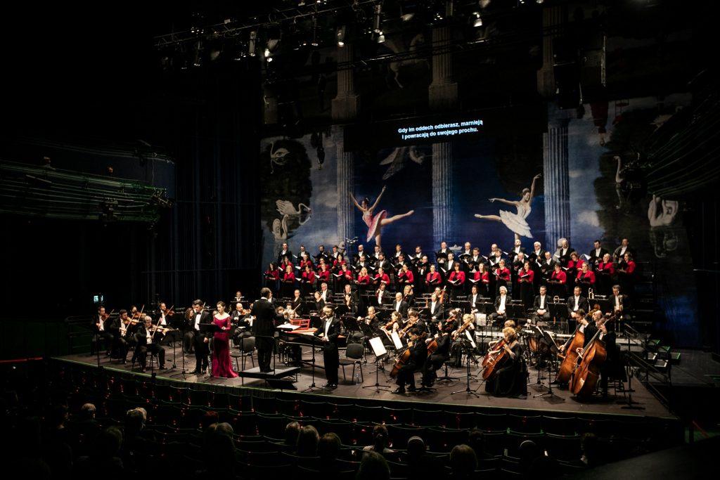 Widok sceny z końca widowni. Z przodu widoczna publiczność tyłem. Na scenie trwa koncert ''Stworzenie Świata''. Z przodu stoją soliści z dyrygentem, za nimi orkiestra. Na końcu stoi w kilku rzędach chór mieszany.
