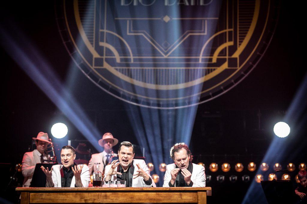 Na scenie , przy drewnianym stole siedzi trzech mężczyzn w białych marynarkach. Wszyscy trzymają ręce przed sobą ułożone w różnych gestach. Za nimi stoi dwóch mężczyzn z instrumentami dętymi. Za nimi, na czarnej kotarze w smugach jasnego światła wyświetlona iluminacja z napisem ''Big Band''.