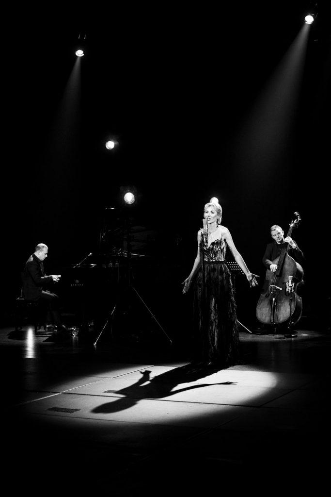 Zdjęcie czarno-białe. Na środku stoi kobieta w długiej sukni w smudze światła. Trzyma ręce rozłożone na boki. Za nią po lewej stronie siedzi mężczyzna przy fortepianie, obok mężczyzna grający na kontrabasie. Z góry widoczne delikatne smugi światła.