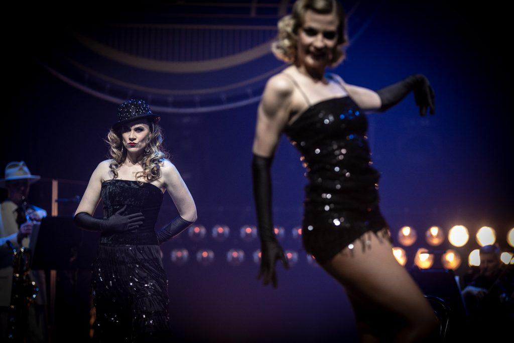 Scena w półmroku. Na scenie dwie kobiety. Jedna w czarnej, błyszczącej sukience i czrnych rękawiczkach stoi bokiem. Druga, nieco dalej, w czarnej sukni i czarnym kapeluszu stoi przodem. Za nimi w dwóch rzędach widoczne reflektory.