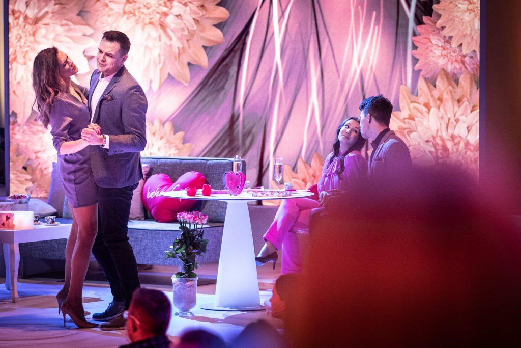 Koncert ''Walentynki z Polsatem''. Na scenie po lewej stronie artyści opery podczas tańca, biorący udział w widowisku. Po prawej stronie, przy białym stoliku siedzi para. Z tylu widoczna szara sofa, na niej leży czerwona poduszka w kształcie serca.