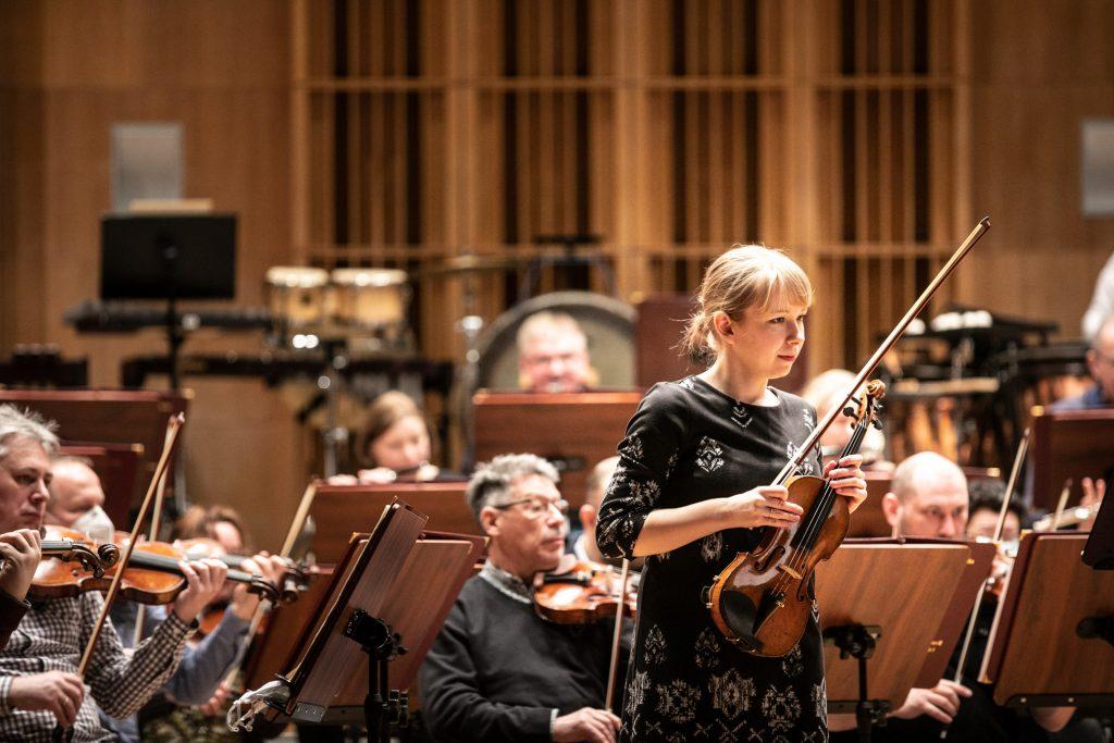 Na środku stoi kobieta ze skrzypcami. Za nią widoczna część orkiestry.
